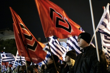 Member of the far right Golden Dawn party hold flags as they take part in a rally in Athens on February 1, 2014. Some 3 000 farright Golden Dawn nationalists took part in the rally to commemorate a 1996 incident between Greece and Turkey at Imia island. Meanwhile anti-fascist protesters clashed with police as they gathered nearby to oppose the rally of members and supportes of the Golden Dawn extreme-right party. AFP PHOTO / Louisa GouliamakiLOUISA GOULIAMAKI/AFP/Getty Images